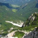 razgled z vrha stene, najprej je travnik z nahrbrniki, nato markirana pot, ki pride iz Žre