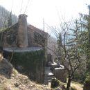 stara hiška z zunanjim dimnikom in majhno teraso, prislonjena ob pobočje