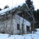 hiša v senčni grapi visoko nad dolino vztrajno propada