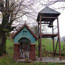 kapelica in nadstrešek z zvonom, ki je ostal od požgane cerkve