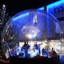glasbeniki v prozorni krogli pred maximarketom