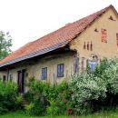 stara, propadajoča hiška, obdana s cvetočim jasminom